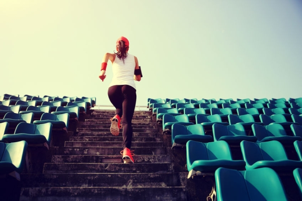 53425133 - runner athlete running on stairs. woman fitness jogging workout wellness concept.