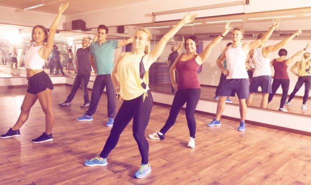 92917925 - happy people exercising zumba elements together in dancing class