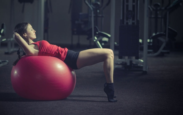 42138469 - young, beautiful, sports girl does exercises on a fitball at the gym. toning.