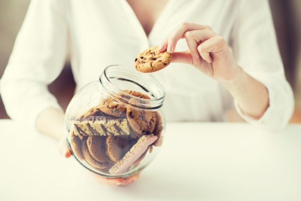 61234968 - people, junk food, culinary, baking and unhealthy eating concept - close up of hands with chocolate oatmeal cookies and muesli bars in glass jar
