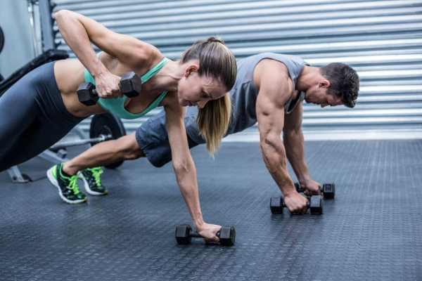 42329057 - muscular couple doing plank exercise while lifting weights