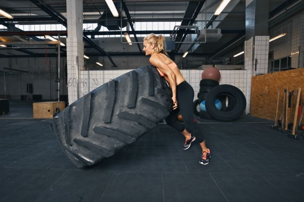 29734040 - fit female athlete flipping a huge tire. muscular young woman doing crossfit exercise at gym.