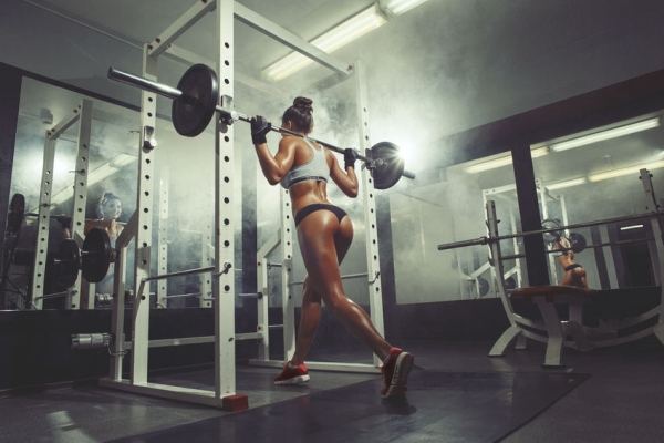 36859768 - sexy young woman resting in the gym and leaning on row of dumbbells