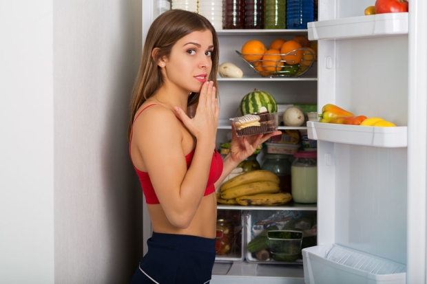 44545181 - woman standing by the fridge and choosing products