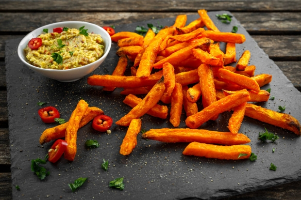 73885568 - healthy homemade baked orange sweet potato fries with guacamole, salt, pepper on stine, stone board