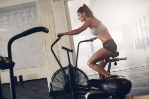58555057 - fit young woman using exercise bike at the gym. fitness female using air bike for cardio workout at crossfit gym.