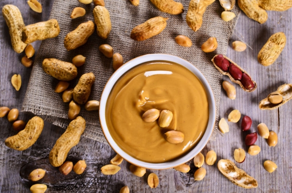 45939673 - peanut butter in a ceramic dish on the background of whole nuts. selective focus.