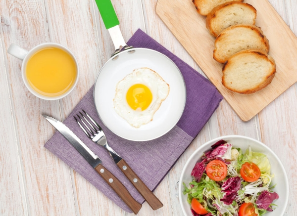 36294863 - healthy breakfast with fried egg, toasts and salad on white wooden table