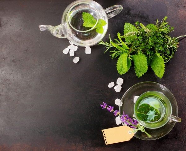 44952212 - freshly brewed peppermint tea with fresh herbal ingredients and flowers alongside in a glass cup and teapot for a refreshing healthy drink, overhead view on slate with copyspace