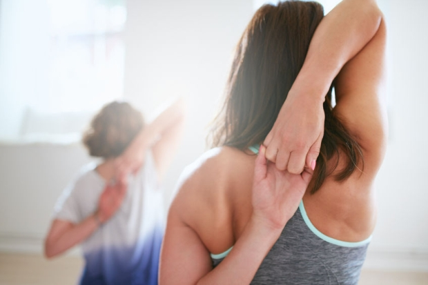 45175321 - rear view of fit woman doing gomukhasana in yoga class. fitness female holding hands behind their back and stretching. triceps and shoulders workout.