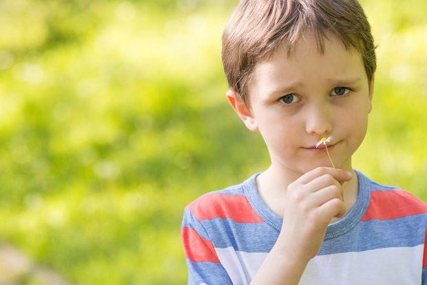 56794078 - children's day.  sweet little boy smelling a daisy in the park