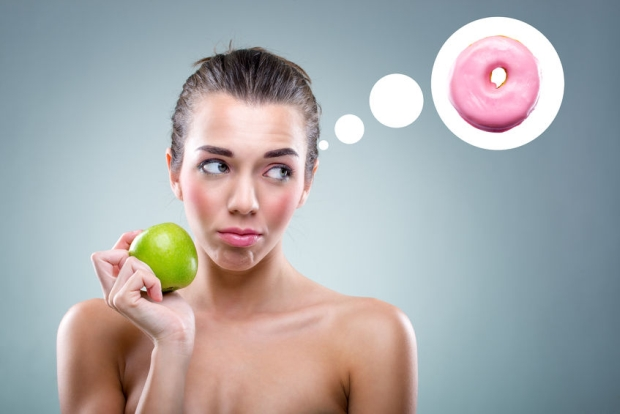 28261900 -  the diet  woman eating an apple , but he thinks a donut