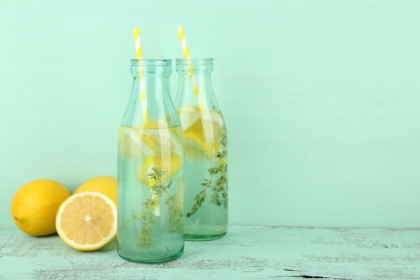 32956099 - tasty cool beverage with lemon and thyme, on wooden background