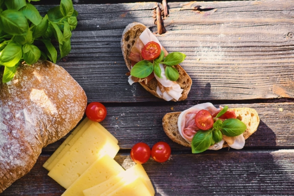 75279429 - brown bread with ham, basil and tomatoes on a grey wooden table.