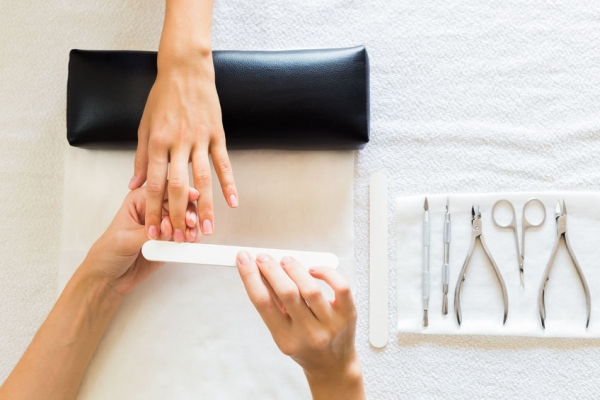 43645208 - beautician performing a manicure in a salon on a lady client filing her nails with a file, view from above of their hands and tools