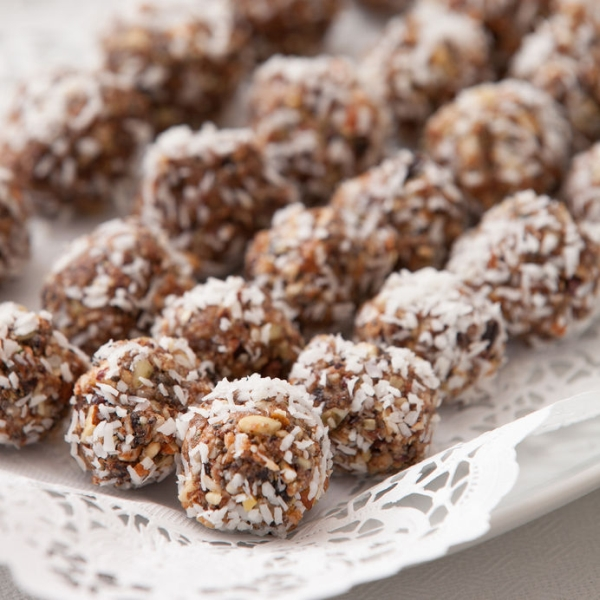 55043627 - white plate full of delicious raw protein balls. healthy sweets for sport people. homemade dessert. raw sweets made of nuts, coconut, dates and cacao