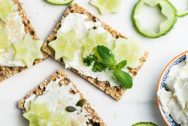 81315475 - healthy snack from wholegrain rye crispbread crackers with ricotta cheese, sesame seeds and pieces of cucumber on the light background
