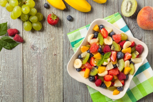 89201967 - delicious fruit salad with fresh fruit. wooden, gray table in the background. top view.