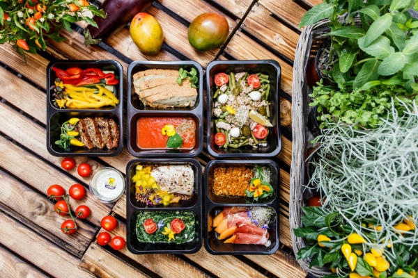 68906761 - healthy food and diet concept, restaurant dish delivery. take away of fitness meal. weight loss nutrition in foil boxes. steamed veal with cous and vegetables at wood