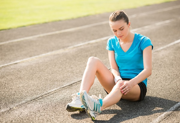 41673513 - female athlete runner touching foot in pain due to sprained ankle.