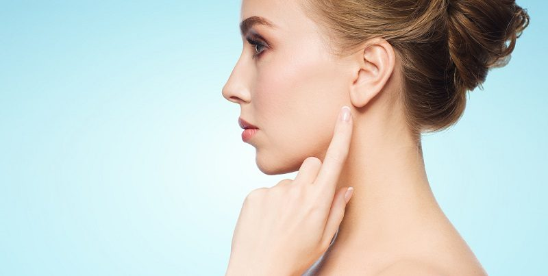 63316572 - health, people and beauty concept - beautiful young woman pointing finger to her ear over blue background