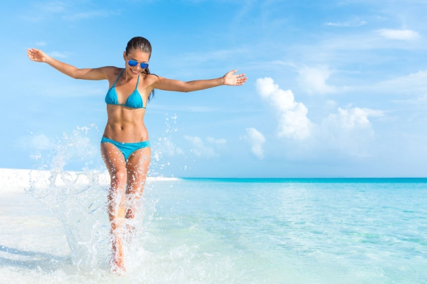 67023669 - sexy bikini body woman playful on paradise tropical beach having fun playing splashing water in freedom with open arms. beautiful fit body girl on luxury travel vacation.