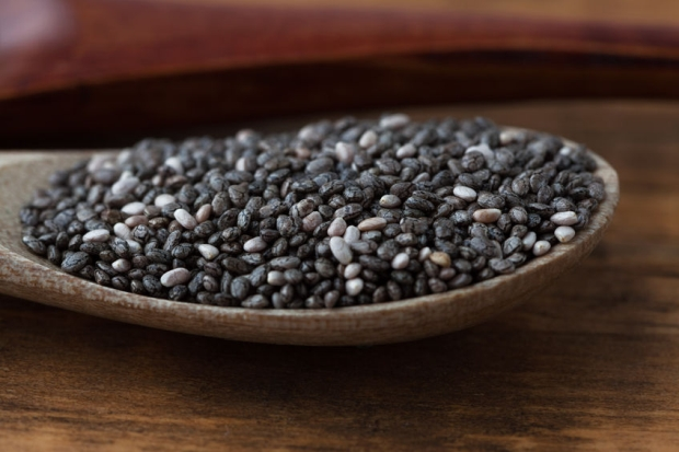79520998 - black chia seeds in wooden spoon extreme closeup