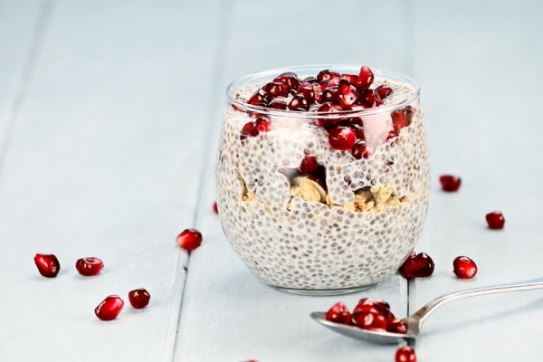 35178204 - chia seed parfait made with pomegranate, oats and almonds with extreme shallow depth of field.