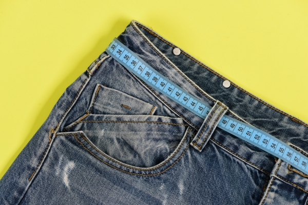 Top part of denim trousers isolated on yellow background. Jeans with blue measure tape instead of belt. Close up of jeans belt loops and pocket. Healthy lifestyle and dieting concept.