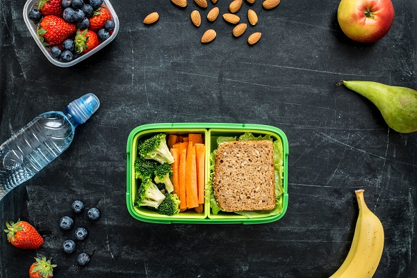 57923542 - school lunch box with sandwich, vegetables, water, almonds and fruits on black chalkboard. healthy eating habits concept - background layout with free text space. flat lay composition (top view).