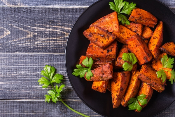 50053261 - homemade cooked sweet potato with spices and herbs on dark background.