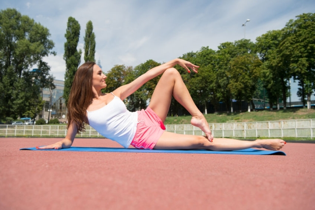 82915070 - summer activity and energy. girl sunny outdoor on fitness mat. coach and health. sport and yoga. woman workout and stretching.