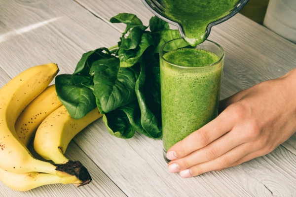 50475535 - female hand pours a smoothie of banana and spinach in glass on a wooden background