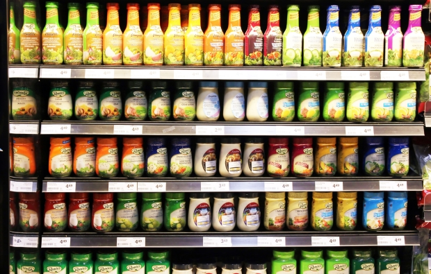 32899762 - variety of salad dressings on shelves in a supermarket