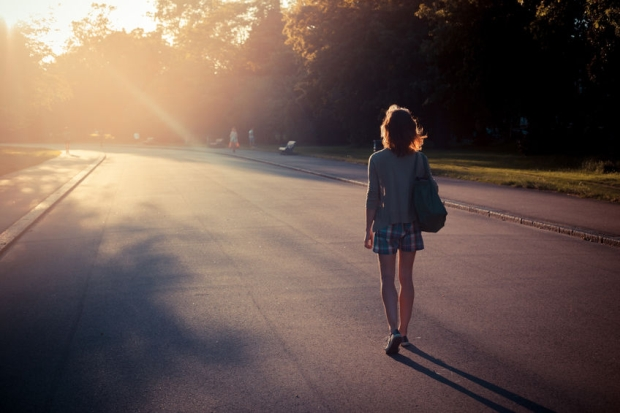 29285039 - a young woman is walking into the sunset in a park