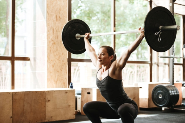 85680116 - sporty concentrated woman exercising with barbell in a gym