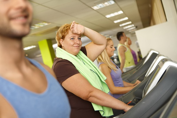 38380863 - exhausted fat woman training on running machine in gym.