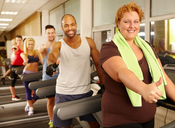 36305541 - fat woman training with others in gym, all showing thumbs up.