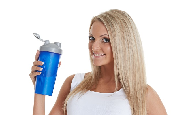 97201772 - the athletic young beautiful  woman with a protein cocktail in a shaker stands on a white background. sports nutrition.