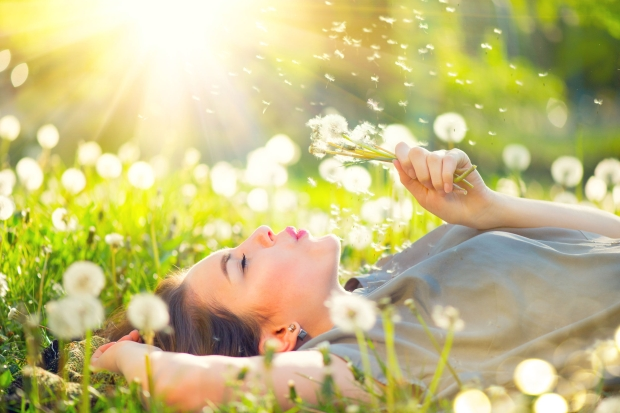 78264157 - beautiful young woman lying on the field in green grass and blowing dandelion