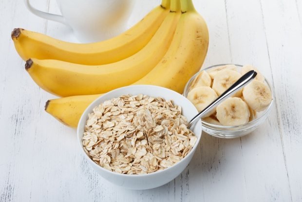 25057874 - bowl of oat flakes with sliced banana close-up on wooden table