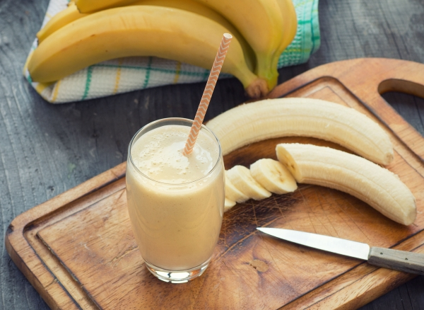 38923233 - fresh made banana smoothie on wooden background