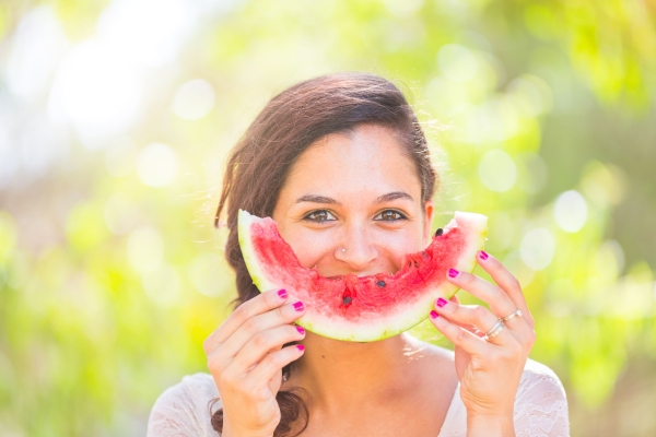 58367827 - beautiful young woman showing a slice of watermelon as a smile. she is caucasian, she wear a white dress and she has a braid on the shoulder. summer and lifestyle concepts.