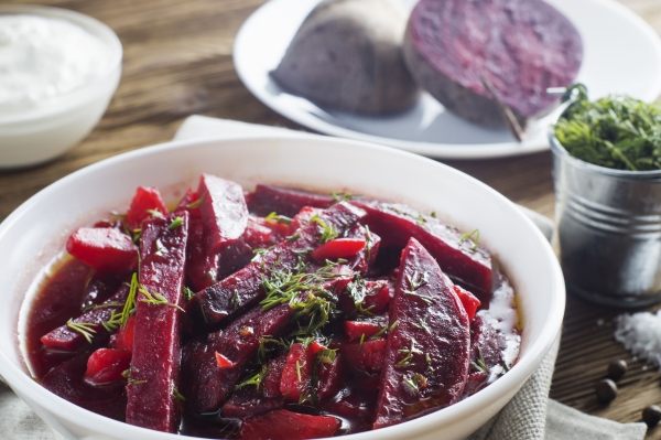 70154117 - vegetable soup - red borsch  in a white bowl on a rustic wooden background, clouse up. healthy beetroot soup, vegetarian food. delicious beet soup with sour cream.