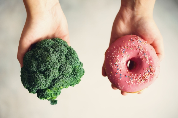 98785106 - young woman in white t-shirt choosing between broccoli or junk food, donut. healthy clean detox eating concept. vegetarian, vegan, raw concept. copy space.