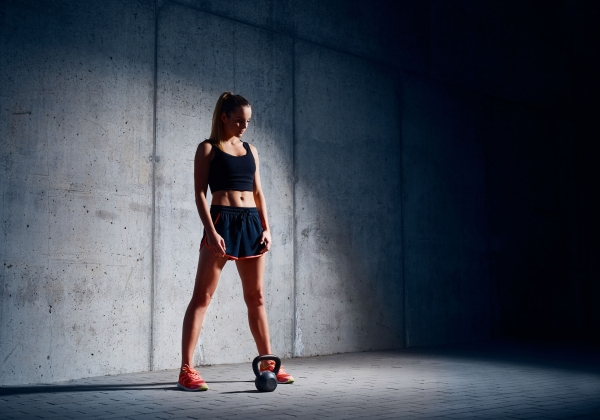 96490590 - sporty woman before kettlebell exercise