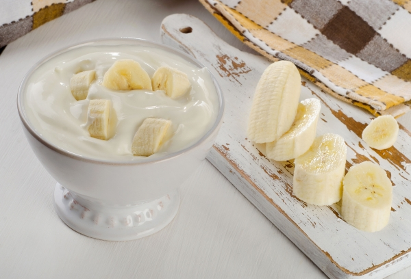 39502562 - yogurt with banana  in a white bowl   on white wooden table.