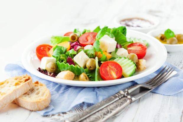 39733767 - fresh summer salad with cherry tomatoes, spinach, arugula, romaine and lettuces in a plate on white wooden background, selective focus