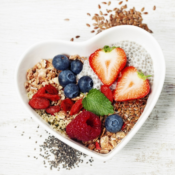 54573017 - healthy breakfast of muesli, berries with yogurt and seeds on white background -  healthy food, diet, detox, clean eating or vegetarian concept.top view