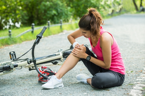 62331851 - young woman with pain in knee when fallen down from bicycle